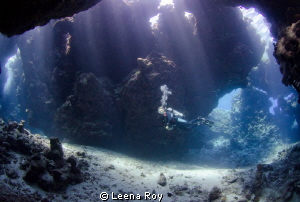 Diver swimming through caves by Leena Roy 